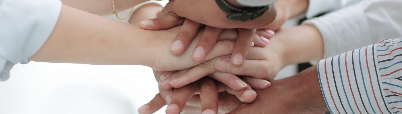 Closeup of business team putting their hands on top of each other.concept of teamwork.